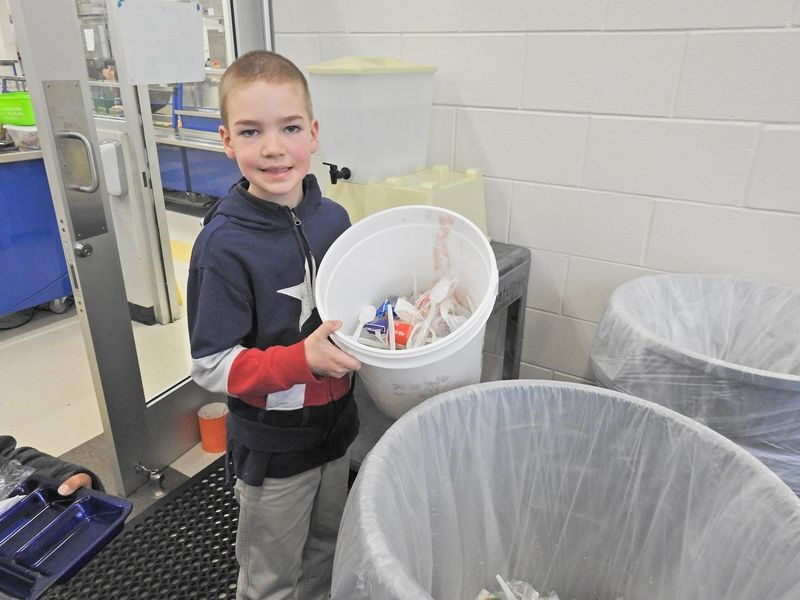 Cherrydale student gathering waste for composting